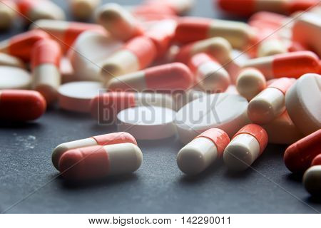 Pharmacy theme Heap of red orange white round capsule pills with medicine antibiotic in packages. Drug prescription for treatment medication. Pharmaceutical medicament, cure in container for health.
