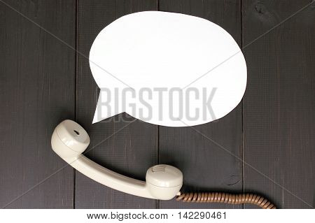 handset lying on a wooden table and departing from it idea talking / sound from telephone handset
