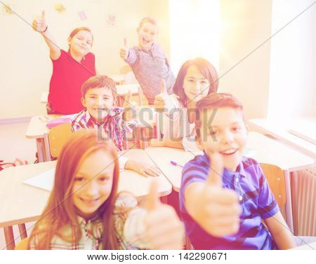 education, elementary school, learning, gesture and people concept - group of school kids sitting in classroom and showing thumbs up