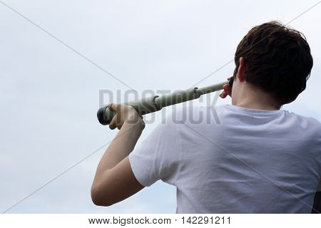 young man looks into the distance across telescope approximating / vision of future