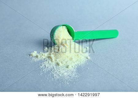 Baby milk formula in spoon on light background