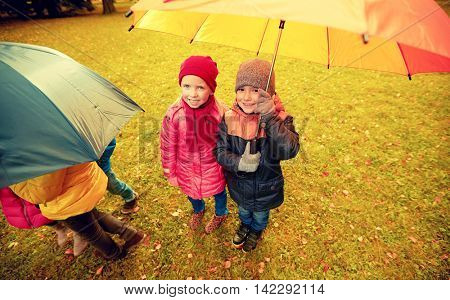 childhood, friendship, season, weather and people concept - group of happy kids with umbrella in autumn park