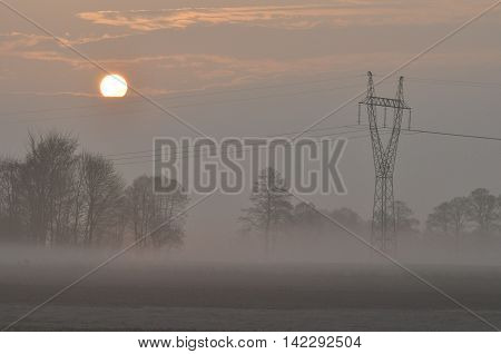 Sunrise. Sunny morning. Line of high-voltage wires and poles.