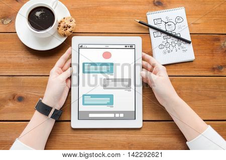 business, education, internet communication, technology and people concept - close up of woman with messenger on tablet pc computer screen and coffee on wooden table