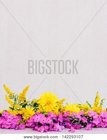 a bouquet of flowers chrysanthemums goldenrod and Phlox on a gray background with space for text. tinted photo