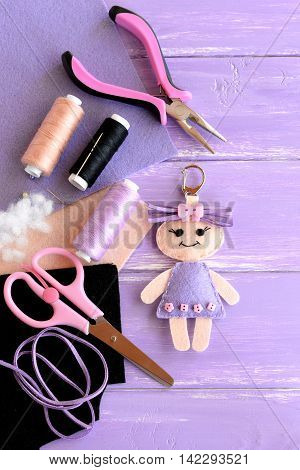 Funny felt doll keychain, pliers, thread set, needle, pins, scissors, hollofayber on wooden background. Sewing supplies for toys. DIY kids embroidery inspiration. Top view
