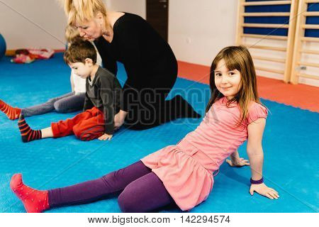 Physical therapist working with group of little children addresing spinal development issues doing simple posture improvement exercises. Cute little girl looking to camera.