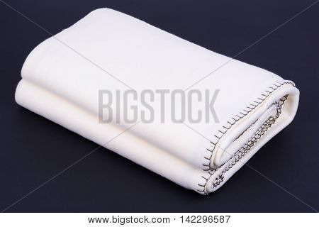 Warm white wool blanket on dark background