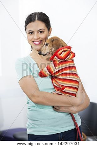 Confident Woman Carrying Ill Dachshund In Clinic