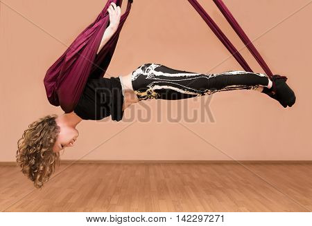 Woman making aerial yoga exercises with hammock fly yoga