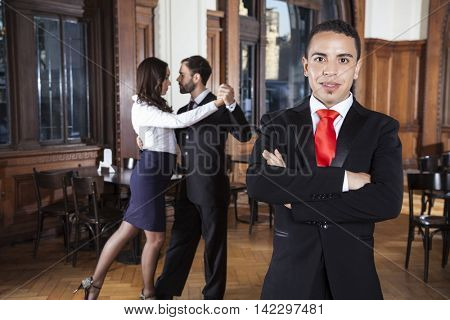 Man With Arms Crossed Standing While Dancers Performing Tango