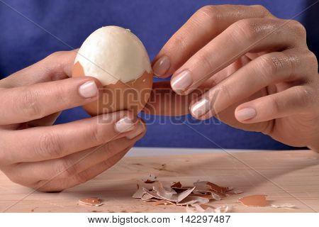 hands peeling boiled egg.Removing egg shell.