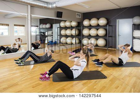 Friends Doing Situps On Hardwood Floor In Gym
