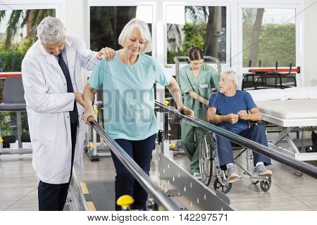 Doctor Helping Woman To Walk Between Bars In Fitness Center