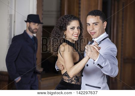 Confident Tango Dancers Performing While Man Standing In Backgro