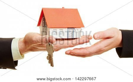 Hands holding a house with keys as a real estate concept