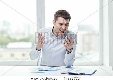 business, people, stress and technology concept - close up of angry businessman with smartphone shouting
