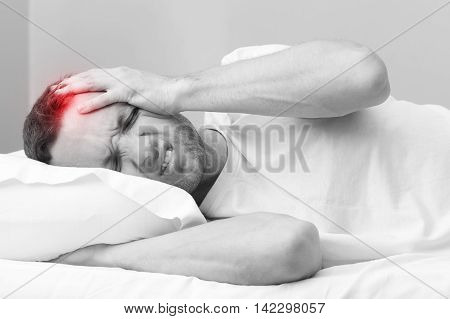 Angry Young Man In Bed With Headache