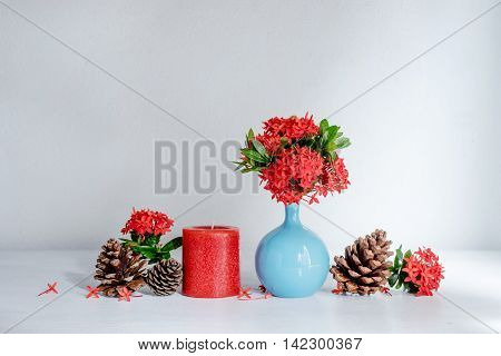 Red ixora flower in blue ceramic vase and red candle on wood table