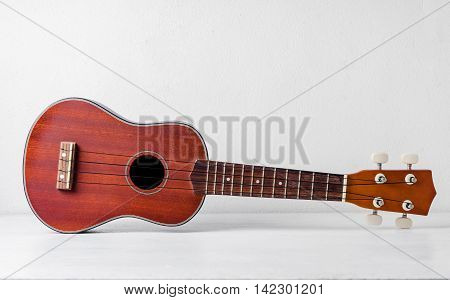The brown ukulele on the table background