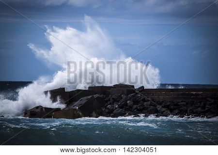 Stone breakwater with breaking waves. Atlantic Ocean