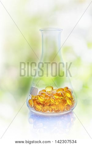 Medical pills in the Erlenmeyer flask on nature background