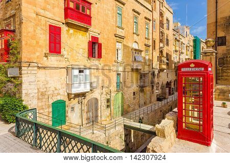 Valletta streetview with red balconies and phone booth - Malta
