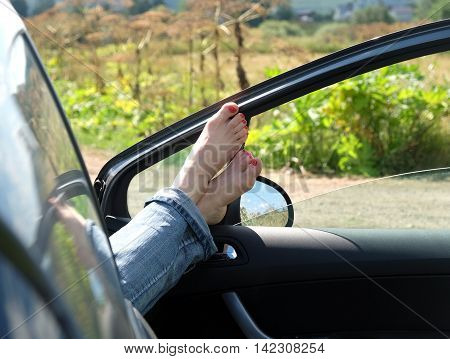 Female feet in jeans rolled up resting placed on opened car door outdoor in rural place in sunny summer day