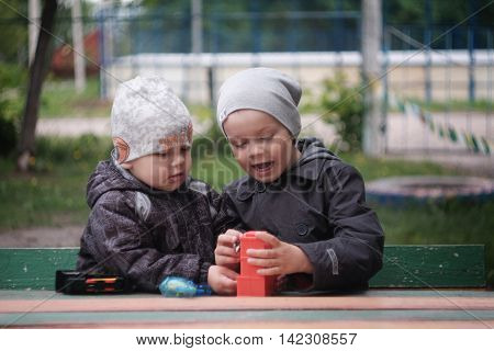 Two boys, enthusiastically playing with toys, sitting at the table outdoors