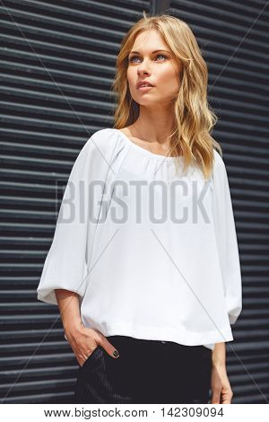 Portrait of beautiful blonde girl in white blouse near gray wall outdors