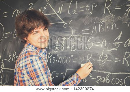 Teenage Boy with chalk writting complicated math formulas on black board, retro toned