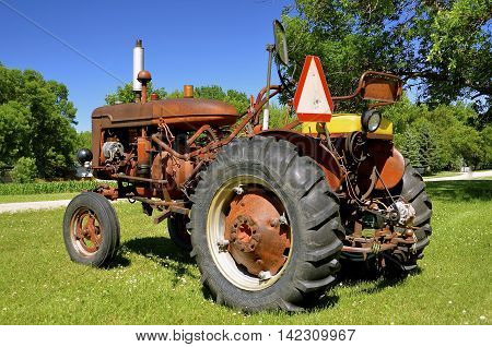 An old working red utility tractor with a slow moving vehicle sign and many other accessories added on