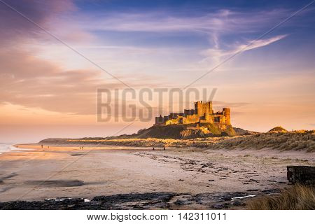Golden Bamburgh Castle, on the Northumberland coastline, bathed in late afternoon golden sunlight