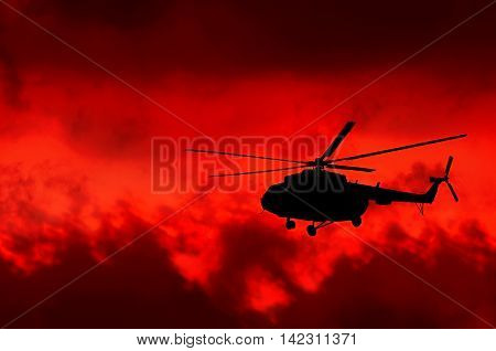 transport helicopter silhouetted against a fiery red sky with clouds
