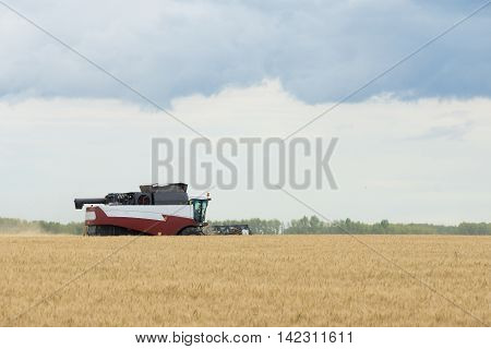 The photograph shows a cleaning combine in the field
