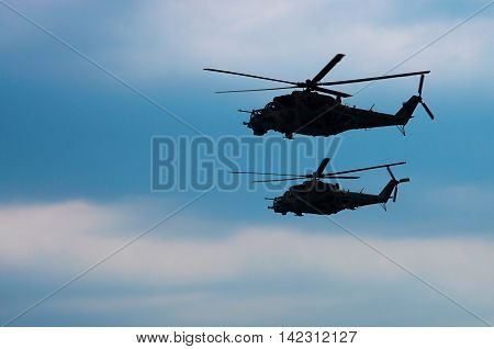 two combat helicopters against the sky with clouds