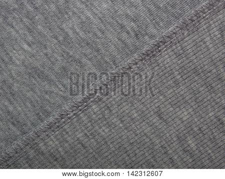 texture of gray fabric with abstract drawings and stitched her seams