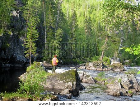 Man in protective helmet and life jacket fishing in mountain river