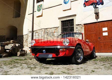 KEZMAROK SLOVAKIA - JULY 08 2016: The red english old car in Kezmarok castle High Tatras Slovakia.