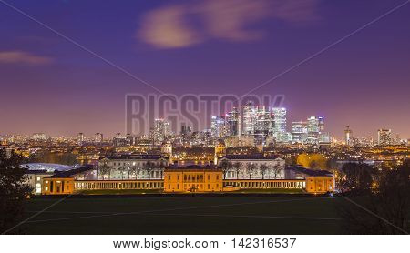 London's National Maritime Museum and skyscrapers of Canary Wharf taken from Greenwich park at dusk - London, UK