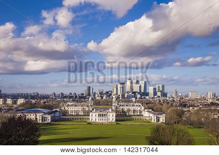 London's National Maritime museum and the famous skyscrapers of Canary Wharf, the leading business district of London, taken from Greenwich park on a beautiful sunny day with clouds - London, UK