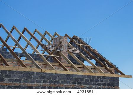 Wooden rafters against the blue sky house