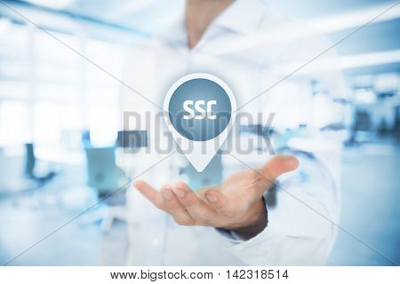 Shared services center (SSC) concept. Businessman hold virtual label with SSC acronym. Double exposed image with office in background.