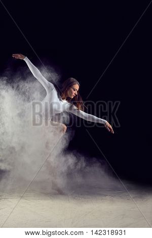 Ballerina dancing with flour on a black background. Dancer in a white bathing suit dancing gracefully with flour. Powder Photo Shoot.
