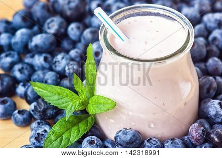 Beautiful appetizer blueberry fruit smoothie milk shake glass jar with juicy fresh berries background top view Yogurt cocktail Natural detox Liquid ice cream hurtleberry huckleberry winberry fraughan