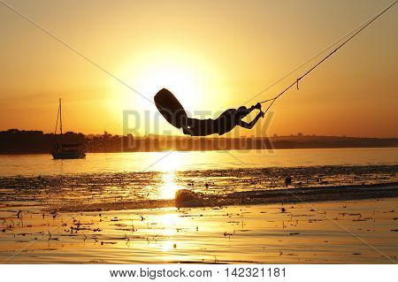 a wakeboard, athlete silhouette on sunset background