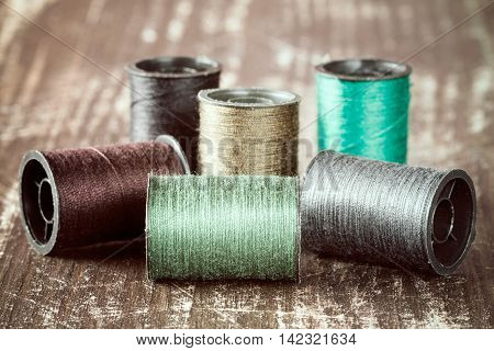Bobbins with colorful threads on wooden background