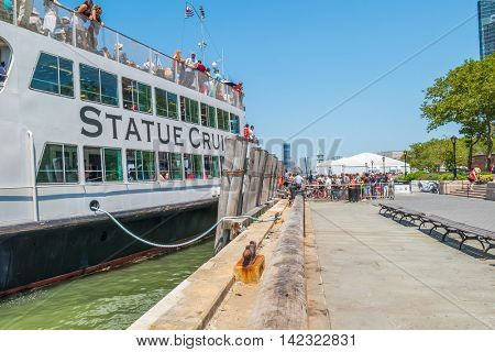 NEW YORK CITY, USA - JUNE 24, 2016: Passengers enter a Statue of Liberty Cruises boat in Battery Park pier