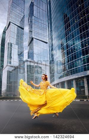 Full growth portrait of fashionable woman in fluttering yellow long dress on urban background