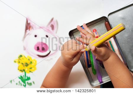 Child's hand is drawing with colorful pencils. Top view.